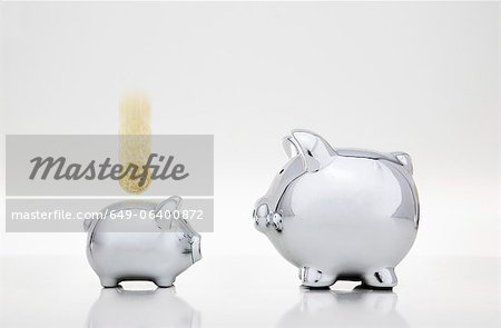 Coin dropping into smaller piggy bank Stock Photo - Premium Royalty-Free, Image code: 649-06400872