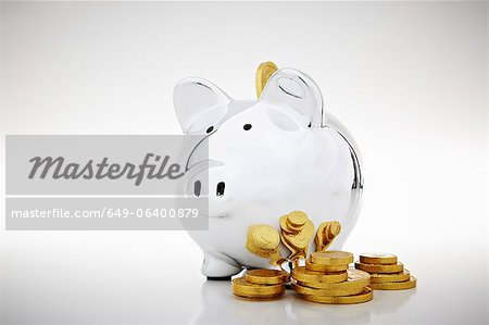 Stack of gold coins by piggy bank Stock Photo - Premium Royalty-Free, Image code: 649-06400879
