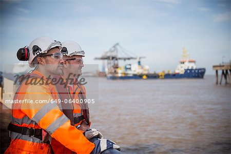Workers on tug boat overlooking ocean Stock Photo - Premium Royalty-Free, Image code: 649-06400905