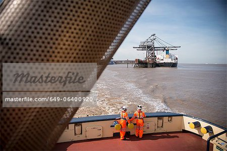 Workers on tug boat overlooking crane Stock Photo - Premium Royalty-Free, Image code: 649-06400920