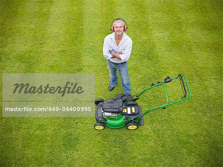 Man standing with lawn mower Stock Photo - Premium Royalty-Free, Image code: 649-06400995