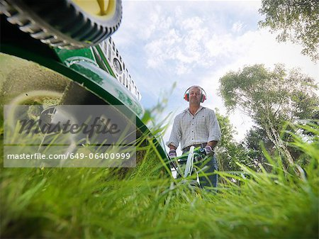 Low angle view of man mowing lawn Stock Photo - Premium Royalty-Free, Image code: 649-06400999