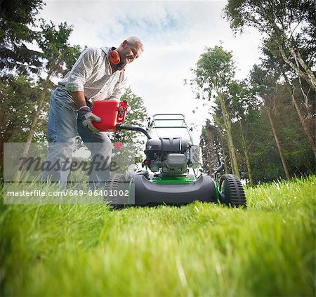 Man pouring gas into lawn mower Stock Photo - Premium Royalty-Free, Image code: 649-06401002