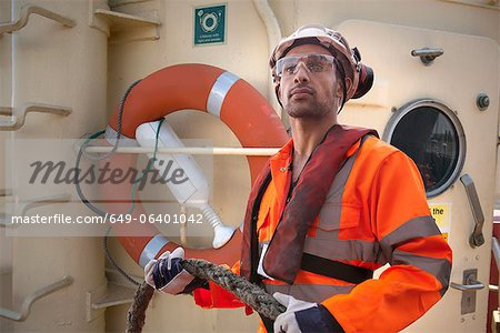 Tugboat worker holding rope on deck Stock Photo - Premium Royalty-Free, Image code: 649-06401042