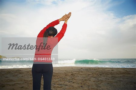 Woman stretching on beach Stock Photo - Premium Royalty-Free, Image code: 649-06401169