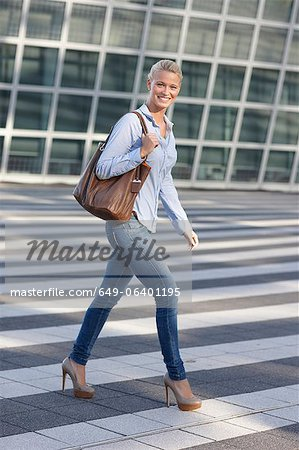 Smiling woman crossing city street Stock Photo - Premium Royalty-Free, Image code: 649-06401195