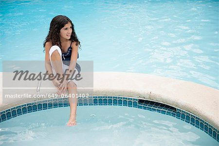 Girl dangling foot in swimming pool Stock Photo - Premium Royalty-Free, Image code: 649-06401402