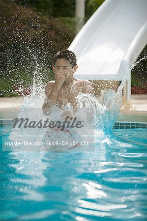 Boy on water slide splashing into pool Stock Photo - Premium Royalty-Free, Image code: 649-06401431