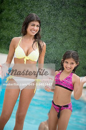 Sisters standing by swimming pool Stock Photo - Premium Royalty-Free, Image code: 649-06401447