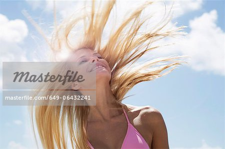 Smiling woman tossing her hair Stock Photo - Premium Royalty-Free, Image code: 649-06432241