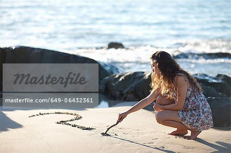 Woman drawing question mark in sand Stock Photo - Premium Royalty-Free, Image code: 649-06432361