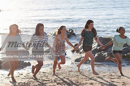 Women holding hands on beach Stock Photo - Premium Royalty-Free, Image code: 649-06432371