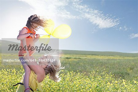 Sisters playing in field of flowers Stock Photo - Premium Royalty-Free, Image code: 649-06432414