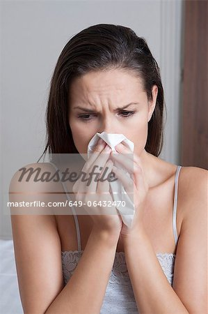 Woman blowing her nose on bed Stock Photo - Premium Royalty-Free, Image code: 649-06432470