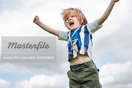 Boy with medals cheering outdoors Stock Photo - Premium Royalty-Free, Image code: 649-06432508