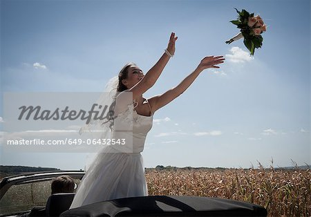 Newlywed bride tossing bouquet from car Stock Photo - Premium Royalty-Free, Image code: 649-06432543