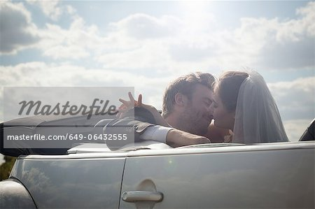 Newlywed couple about to kiss in a convertible Stock Photo - Premium Royalty-Free, Image code: 649-06432555