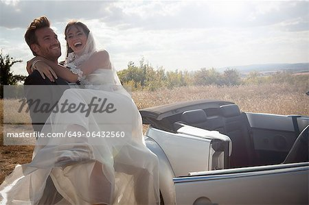 Newlywed groom carrying bride outdoors Stock Photo - Premium Royalty-Free, Image code: 649-06432560