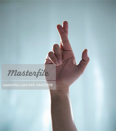 Close up of hand with crossed fingers Stock Photo - Premium Royalty-Free, Image code: 649-06432978