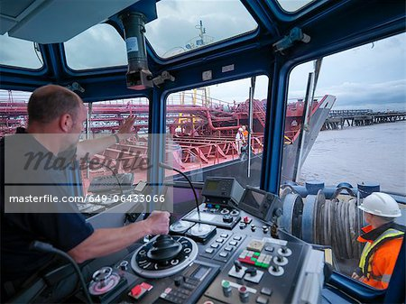 Worker driving tugboat in wheelhouse Stock Photo - Premium Royalty-Free, Image code: 649-06433066