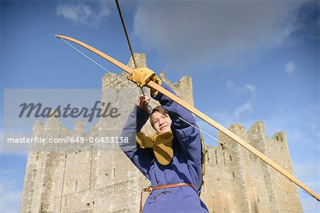 Student in period dress shooting arrow Stock Photo - Premium Royalty-Free, Image code: 649-06433138