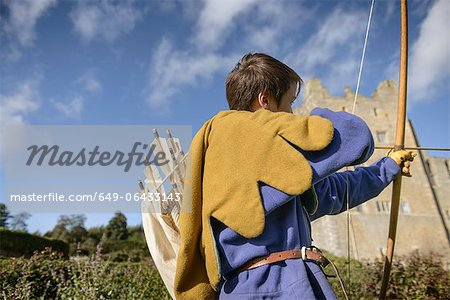Student in period dress shooting arrow Stock Photo - Premium Royalty-Free, Image code: 649-06433143