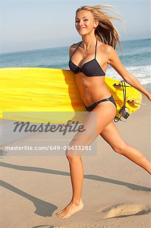 Woman carrying surfboard on beach Stock Photo - Premium Royalty-Free, Image code: 649-06433281