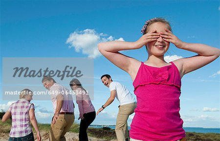 Family playing hide and seek outdoors Stock Photo - Premium Royalty-Free, Image code: 649-06433491