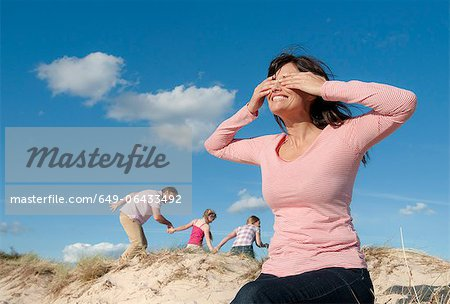 Family playing hide and seek outdoors Stock Photo - Premium Royalty-Free, Image code: 649-06433492