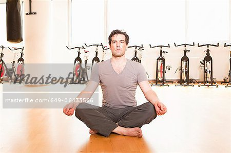 Man meditating on mat at gym