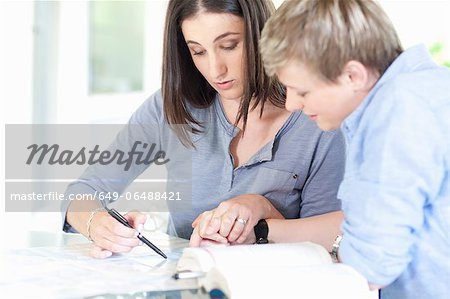 Women working together at desk Stock Photo - Premium Royalty-Free, Image code: 649-06488421