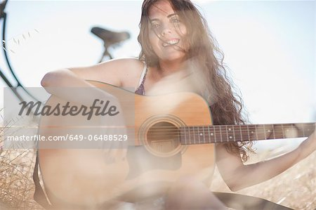 Woman playing guitar in tall grass Stock Photo - Premium Royalty-Free, Image code: 649-06488529