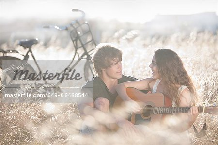 Woman playing guitar for boyfriend Stock Photo - Premium Royalty-Free, Image code: 649-06488544