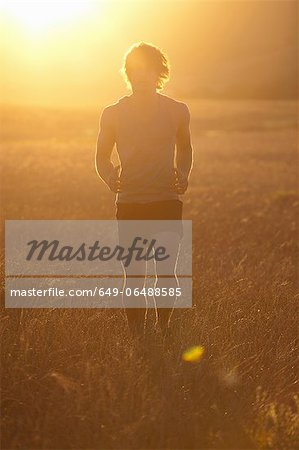 Man running in tall grass at sunset Stock Photo - Premium Royalty-Free, Image code: 649-06488585