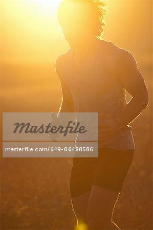 Man running in tall grass at sunset Stock Photo - Premium Royalty-Free, Image code: 649-06488586