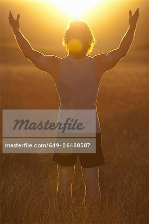 Man standing in field at sunset Stock Photo - Premium Royalty-Free, Image code: 649-06488587