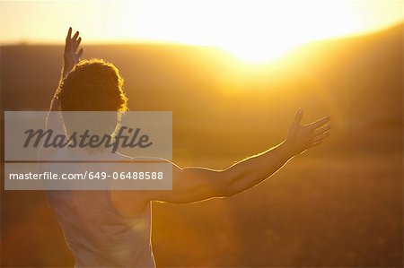 Man standing in field at sunset Stock Photo - Premium Royalty-Free, Image code: 649-06488588