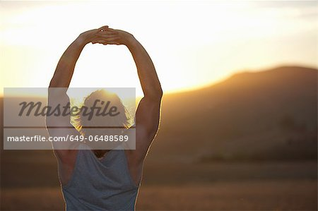 Man stretching in field at sunset Stock Photo - Premium Royalty-Free, Image code: 649-06488589
