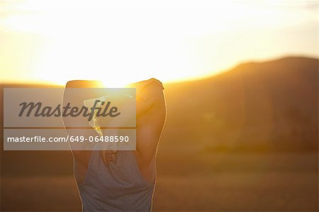 Man stretching in field at sunset Stock Photo - Premium Royalty-Free, Image code: 649-06488590