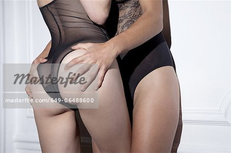 Woman touching girlfriends buttocks Stock Photo - Premium Royalty-Free, Image code: 649-06488600
