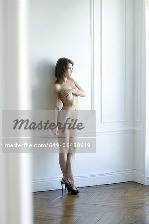 Nude woman leaning against wall Stock Photo - Premium Royalty-Free, Image code: 649-06488619