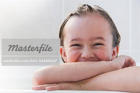 Smiling girl sitting in bath Stock Photo - Premium Royalty-Free, Image code: 649-06489047