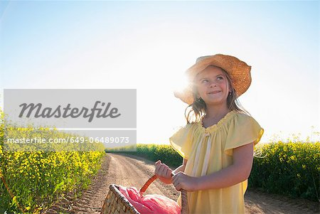 Girl carrying basket on dirt road Stock Photo - Premium Royalty-Free, Image code: 649-06489073