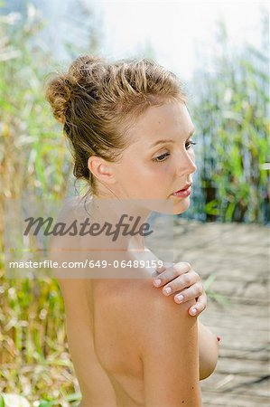 Nude woman standing in riverbank Stock Photo - Premium Royalty-Free, Image code: 649-06489159