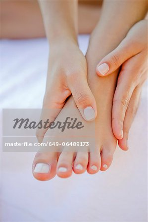 Close up of woman rubbing her foot Stock Photo - Premium Royalty-Free, Image code: 649-06489173