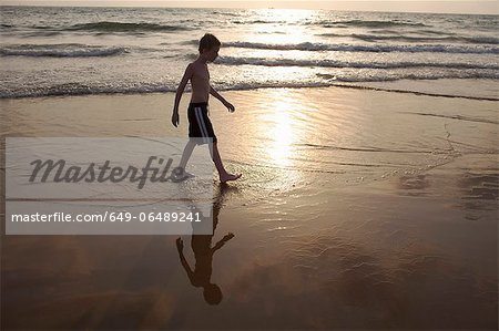 Boy walking in waves on beach Stock Photo - Premium Royalty-Free, Image code: 649-06489241