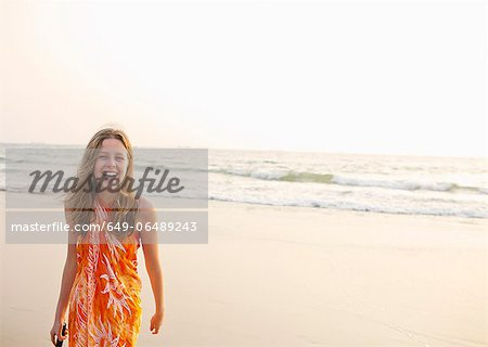 Smiling girl walking on beach Stock Photo - Premium Royalty-Free, Image code: 649-06489243