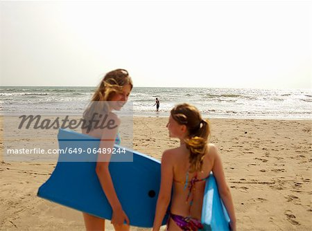 Girls carrying boogie boards on beach Stock Photo - Premium Royalty-Free, Image code: 649-06489244
