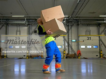 Worker carrying boxes in warehouse Stock Photo - Premium Royalty-Free, Image code: 649-06489259