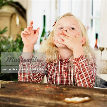 Girl eating Christmas cookies in kitchen Stock Photo - Premium Royalty-Free, Image code: 649-06489289